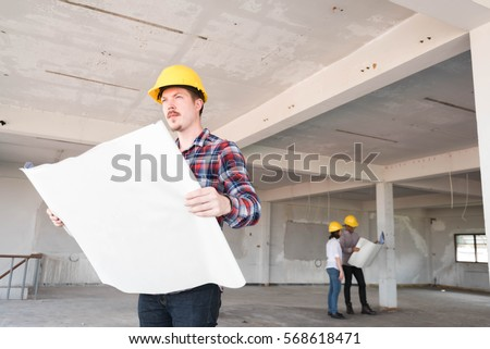 Close up Construction engineer wear yellow safety helmet with blue print of construction plan in hand #568618471