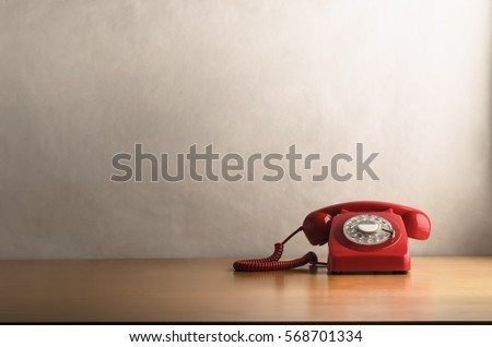 Eye level shot of a retro red telephone (British circa 1960s to 1970s) on a light wood veneer desk or table with off white background providing copy space. Royalty-Free Stock Photo #568701334