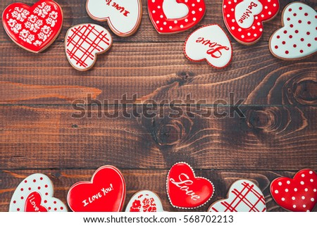 Heart-shaped biscuits for Valentine's Day. Framework with Gingerbread Valentine on wooden background #568702213