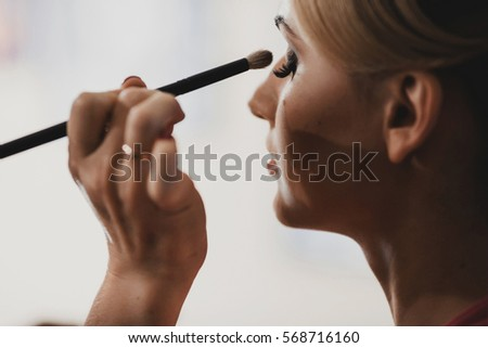 The makeup artist doing a makeup for bride #568716160