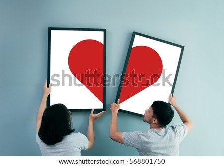 Valentine's day concept. Asian couple holding picture frames with red heart on blue wall background. Young Man and Woman decorating wall during moving new house. Rear view of lover.