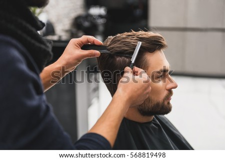 Male client getting haircut by hairdresser Royalty-Free Stock Photo #568819498