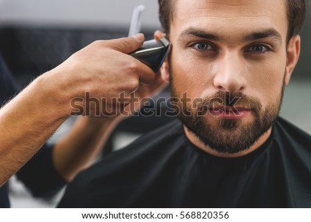 Confident guy sitting at beauty salon Royalty-Free Stock Photo #568820356