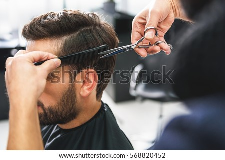 Barber using scissors and comb Royalty-Free Stock Photo #568820452