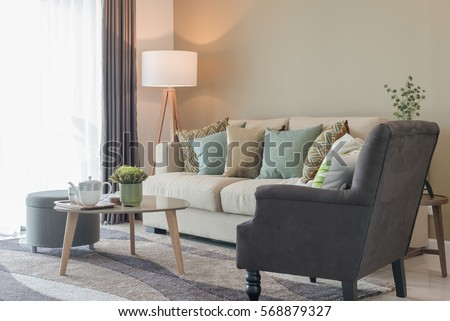 modern living room with green pillows on cozy sofa and wooden lamp, interior design #568879327