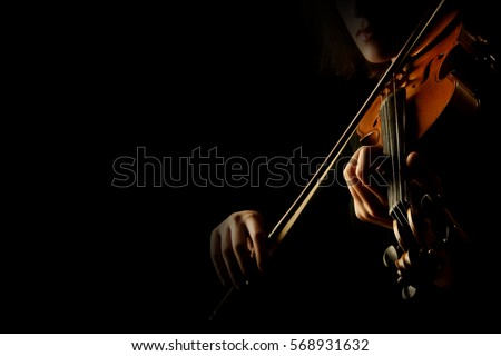 Violin player hands. Violinist playing violin isolated on black. Close up of musical instruments #568931632