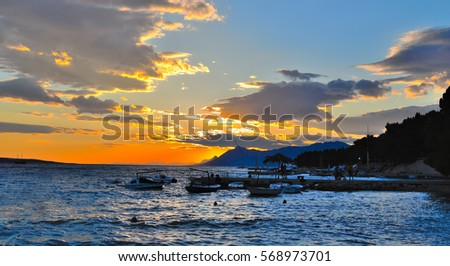 Orange sunset in Makarska Riviera. Dalmatia, Croatia. #568973701