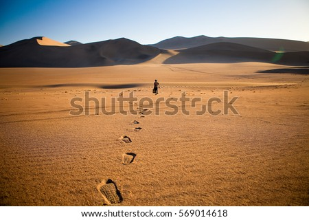 Walking alone in the desert with footsteps #569014618