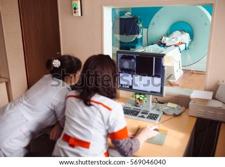 MRI machine and screens with doctor and nurse #569046040