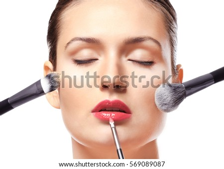Beautiful girl applying cosmetics on white background #569089087