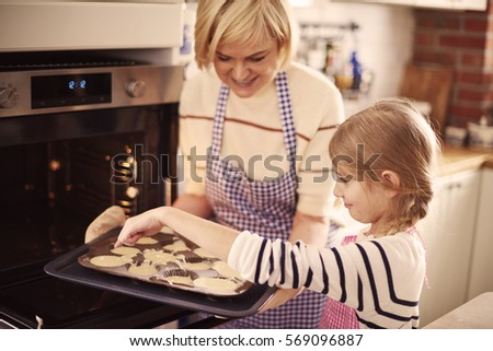 Litlle girl helping grandmother while baking 