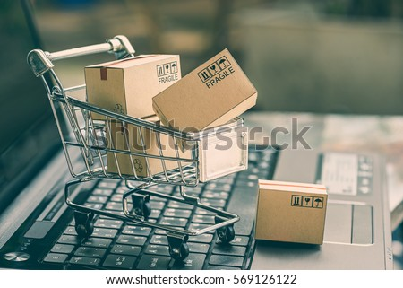 Cartons in a shopping cart on a laptop keyboard. Ideas about online shopping, online shopping is a form of electronic commerce that allows consumers to directly buy goods from a seller over internet. Royalty-Free Stock Photo #569126122