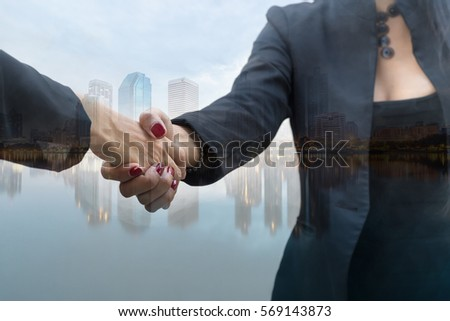 Double exposure of two business people handshake and city with marketing online concept #569143873