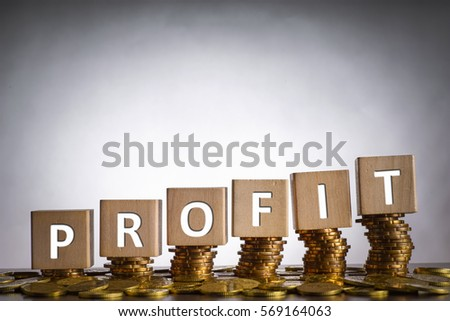 Wooden cube written PROFIT with stacked coins                                #569164063
