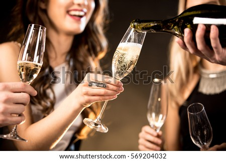 Partial view of happy young friends drinking champagne  #569204032