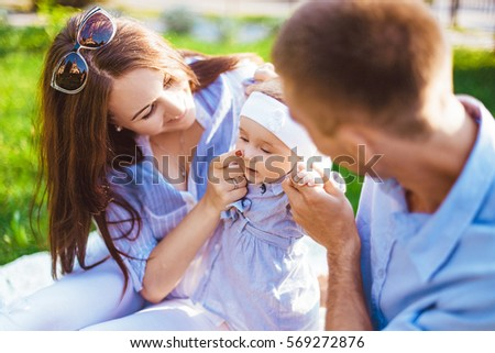 Happy caucasian family outdoors. Mother, father and child playing #569272876