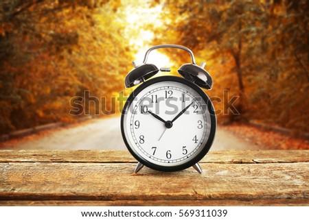 Alarm clock on wooden table against landscape background. Time change concept #569311039
