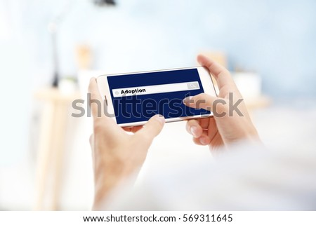 Adoption concept. Male hands with smartphone and search box on screen #569311645