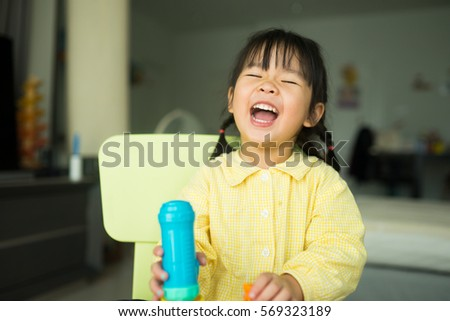 Happy little asian girl laugh and smile.children's creativity. child sculpts from clay.Cute little girl moulds from plasticine on table.Dentist Concept. #569323189