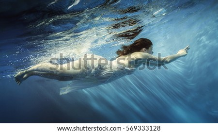 Pregnant young woman in a dress floats under water #569333128