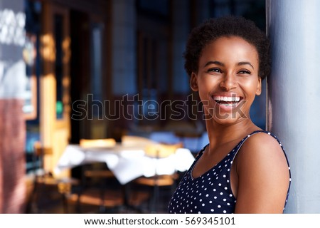 Side portrait of smiling young black woman standing outside Royalty-Free Stock Photo #569345101
