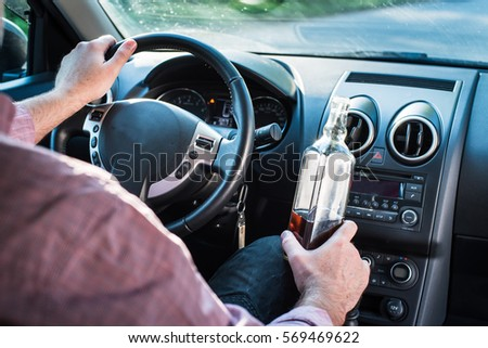 In the picture a man drinking alcohol in the car. #569469622