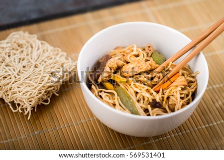 Dried Chinese noodles with meat in the dish. Bamboo chopsticks. Asian cuisine. #569531401