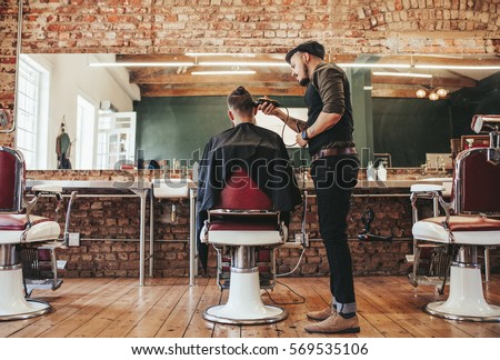 Rear view shot of handsome hairdresser cutting hair of male client. Hairstylist serving client at barber shop. #569535106