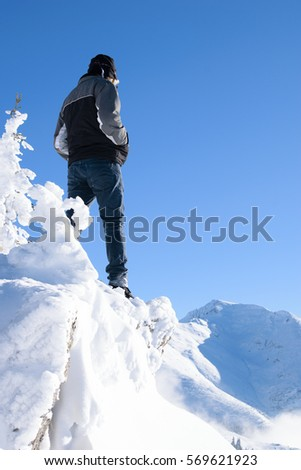 Man high on a mountain cliff in winter time. Leader, winner concept #569621923