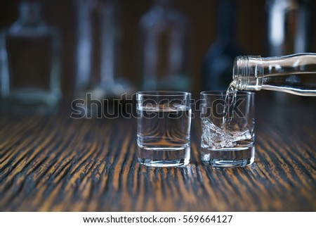 Russian vodka pouring from the bottle into two shot  glass in a bar, selective  focus #569664127