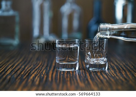 Russian vodka pouring from the bottle into glass in a bar, selective  focus #569664133