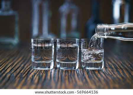 Russian vodka pouring from the bottle into three shot  glass in a bar, selective  focus #569664136