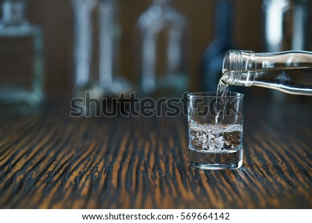 Russian vodka pouring from the bottle into glass in a bar, selective  focus