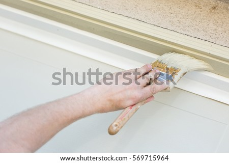 Professional Painter Cutting In With A Brush to Paint Garage Door Frame. #569715964