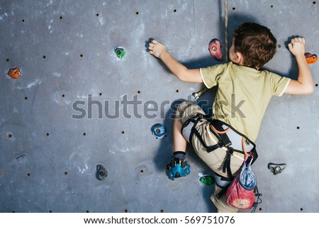 little boy climbing a rock wall indoor. Concept of sport life. Royalty-Free Stock Photo #569751076