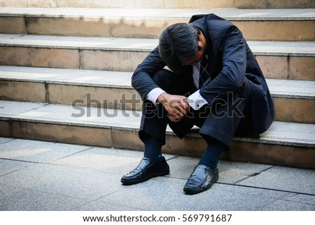Stressed businessman sitting at stairway outdoor.Bankrupt businessman sitting outdoor. Royalty-Free Stock Photo #569791687