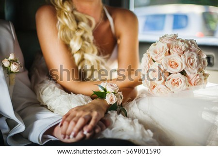 Bride and bridegroom sitting in car and holding hands. Bridal bouquet of beige roses in womans hand with bracelet boutonnieres. Fiancee in wedding dress with elegant round bunch of fresh roses. #569801590