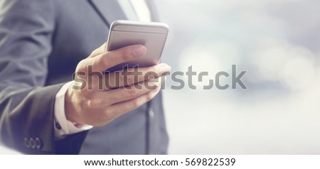 Close up of a business man using mobile smart phone, copy space. Royalty-Free Stock Photo #569822539