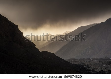 Beautiful sunset in mountains with fog and mountain silhouette #569874820
