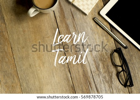 Education concept. Top view of tablet, glasses. notebook pen and a cup of coffee with LEARN TAMIL written on wooden background. #569878705