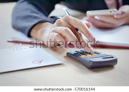 close view of a business woman hand calculating her monthly expenses during tax season. Royalty-Free Stock Photo #570016144