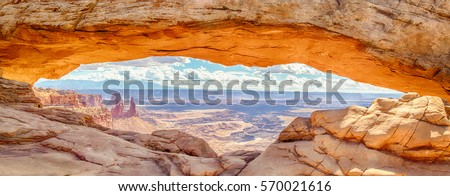 Panoramic view of famous Mesa Arch, iconic symbol of the American West, illuminated golden in beautiful morning light on a sunny day with blue sky and clouds, Canyonlands National Park, Utah, USA #570021616