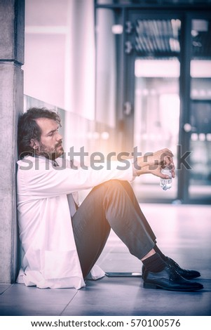 Doctor holding water bottle while sitting on floor at hospital #570100576