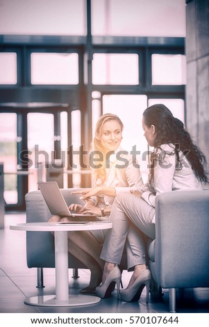 Businesswomen using laptop and having discussion in office #570107644