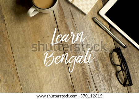 Education concept. Top view of tablet, glasses. notebook pen and a cup of coffee with LEARN BENGALI written on wooden background. #570112615