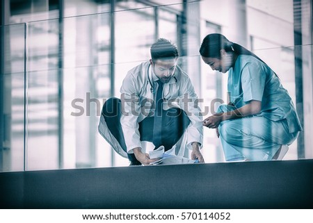 Doctor and nurse collecting fallen medical reports in hospital #570114052