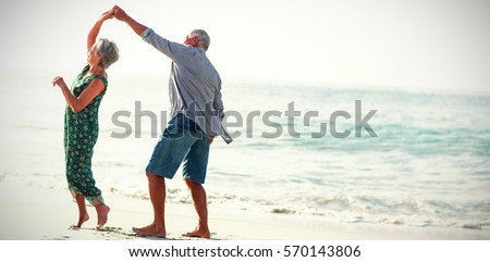 Senior couple dancing at beach on sunny day Royalty-Free Stock Photo #570143806