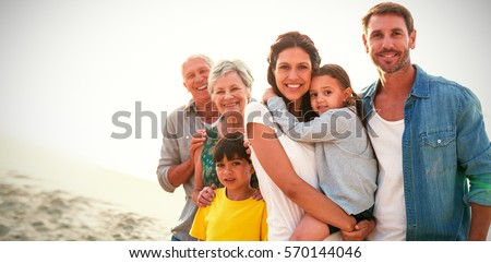 Portrait of happy family standing at beach Royalty-Free Stock Photo #570144046