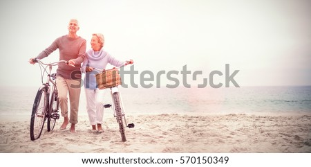 Full length of senior couple with their bicycles at the beach Royalty-Free Stock Photo #570150349