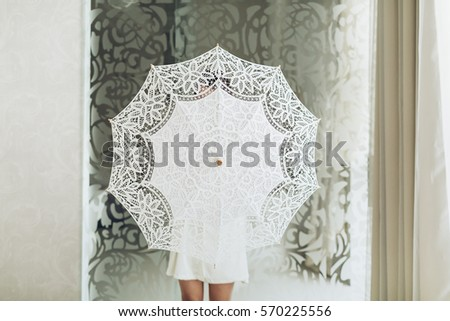 White fabric umbrella in hands. Studio photo